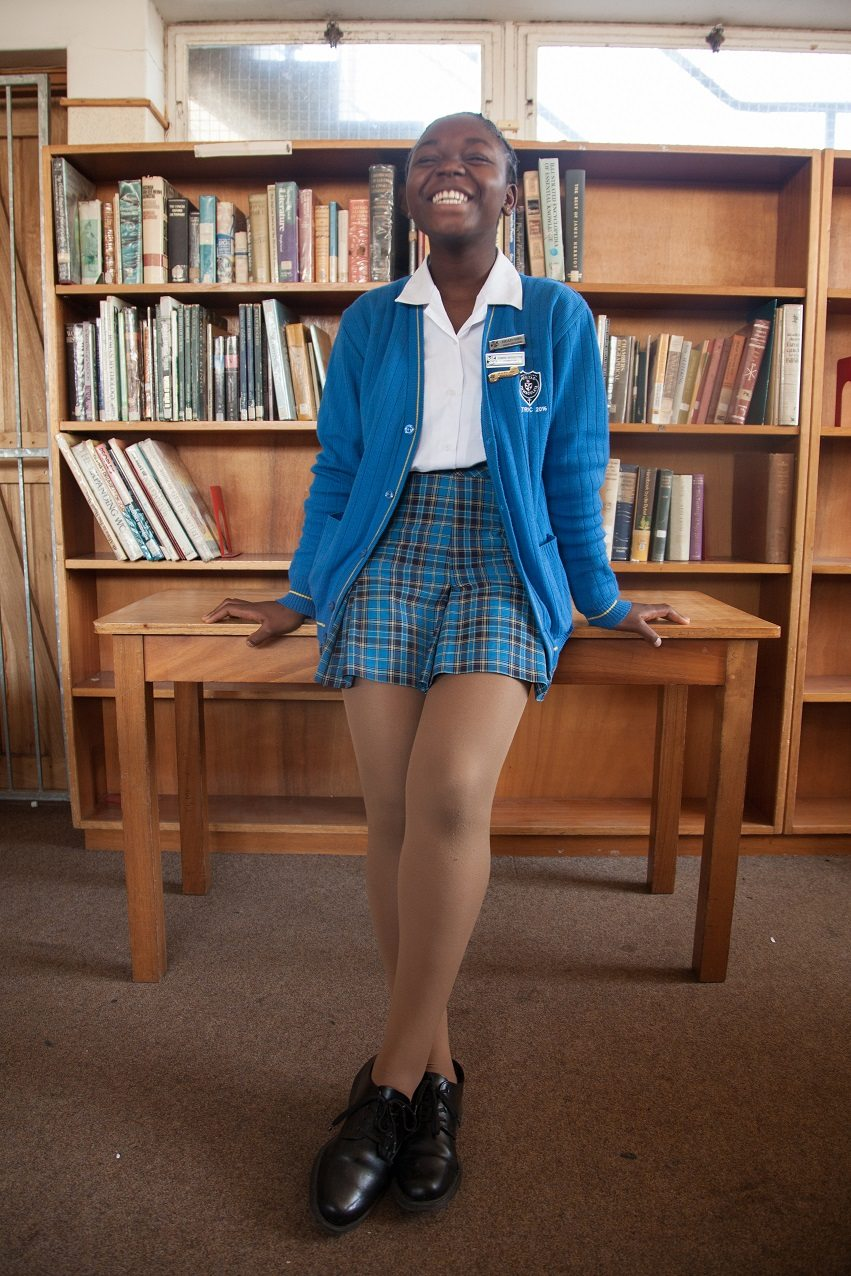 Mimi Ibrahim in her school's library. Through donations from the Cape Town public, Mimi is slowly starting to replace the outdated books behind her with books that are more applicable to youths at her school.